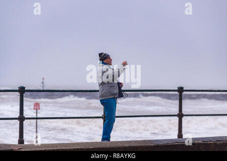 Sidmouth, Devon, 15th Dec 18 Despite gale force winds and driving rain, a man takes photos of the stormy conditions on Sidmouth seafront. Photo Central / Alamy Live News - Stock Image