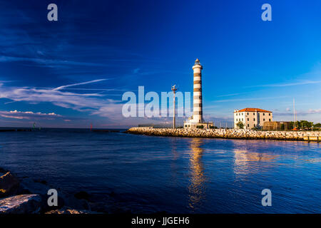 View at the lighthouse in the bay with beautiful blue sky. Sunrise time. Jesolo, Italy. - Stock Image
