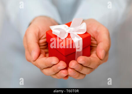 Small red present box in hands - Stock Image