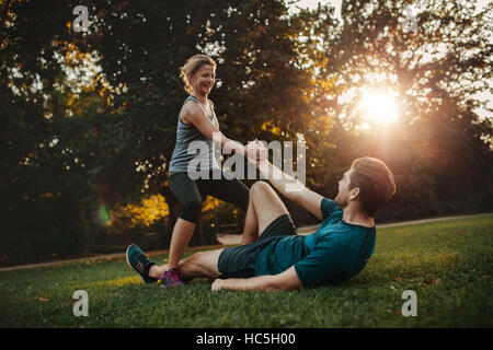 Shot of young woman helping man to get up from ground. Healthy young couple at park exercising together. - Stock Image