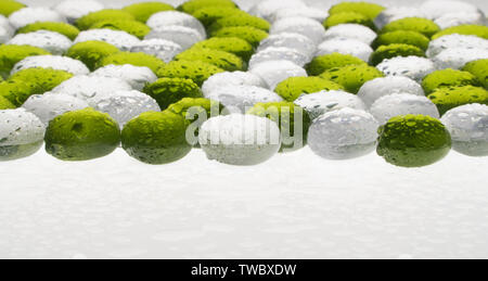 artificial round stones with water drop of green and white color. imitation pebbles - Stock Image