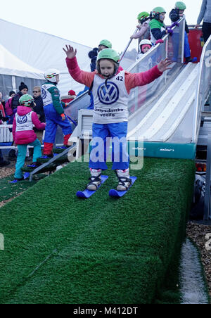 A young girl lands after the jump on the 'baby ski jumping hill' for children. Ljubno ob Savinji, Slovenia. - Stock Image