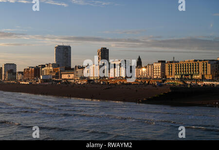 View of Brighton seafront and beach at sunset with sun shining on iconic seaside buildings - Stock Image