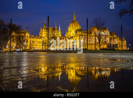 Budapest, Hungary - Illuminated Parliament of Hungary at blue hour with reflection - Stock Image