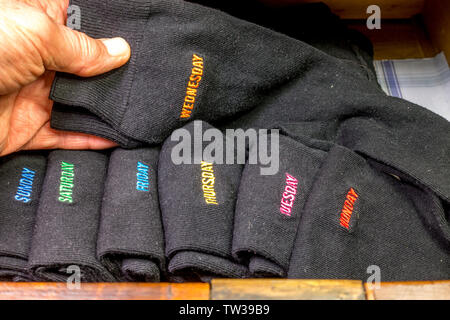 A man's hand arranging stylish plain dark socks in a drawer, but with each pair from the seven in total being embroidered with a day of the week. - Stock Image