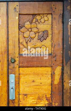 Ornate hand carved heavy old varnished wooden door with Dogwood Flower design. in British Columbia, Canada. - Stock Image