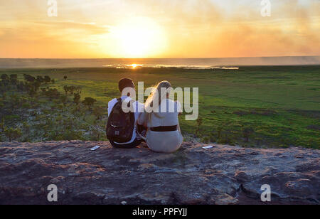 Two young people sit on the rocks at Ubirr Lookout to watch the sunset Kakadu National Park, Northern Territory, Top End, Australia - Stock Image