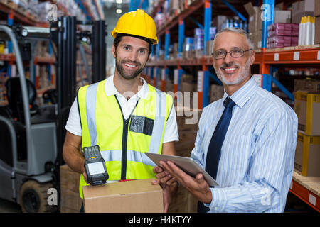Warehouse manager holding digital tablet while male worker scanning barcode - Stock Image