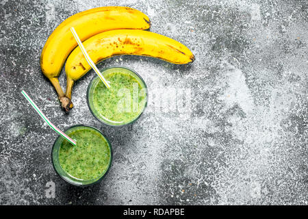 Green smoothie with spinach and banana. On rustic background. - Stock Image