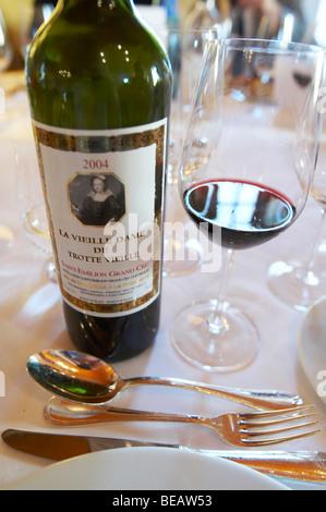 bottle and glass with wine at dinner table la vieille dame de chateau trottevieille saint emilion bordeaux france - Stock Image