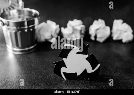 recycle symbol surrounded by scrunched paper balls with garbage bin, concept of reducing damage to the environment - Stock Image