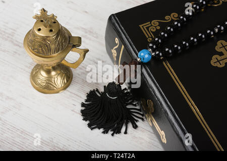 Closeup of Holy Bible, rosary beads with cross and incense burner on white wooden background. Religion concept and faith. - Stock Image