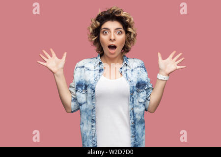 Portrait of surprised young woman with curly hairstyle in casual blue shirt standing with big eyes, open mouth and looking at camera with raised arms. - Stock Image