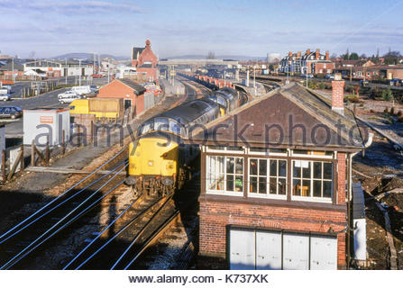 Freight train hauled by two Class 37 diesel locomotives (37502 and 37203) passing by the signal box at Hereford Station, England, UK. - Stock Image