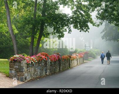 On a misty morning, couple walking on Albert Meadow street, Bar Harbor, Maine, USA. - Stock Image