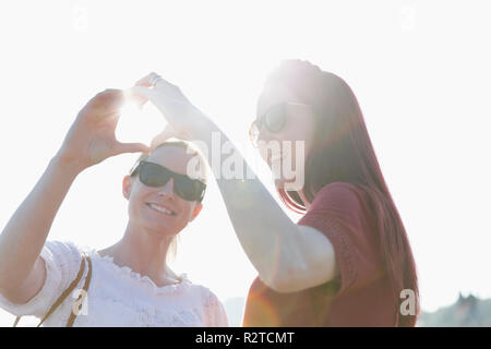 Affectionate lesbian couple forming heart-shape with hands - Stock Image