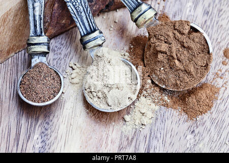 Measuring spoon filled with pumpkin pie spice ingredients with Cinnamon, Ginger and Nutmeg over a rustic wooden background. Extreme shallow depth of f - Stock Image