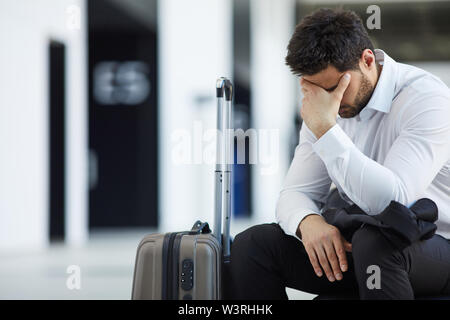 Sad handsome young businessman in white shirt sitting with wheeled luggage in airport and crying because of being late on plane - Stock Image