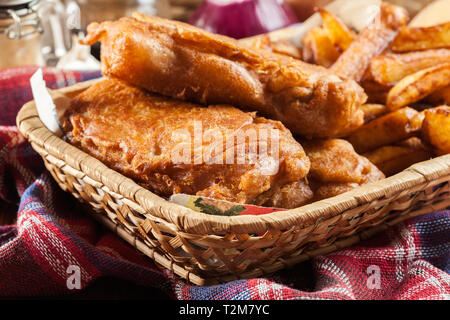 Traditional fish in beer batter and chips served on basket - Stock Image