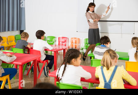Friendly smiling teacher explaining studying material to children during lesson at elementary school - Stock Image
