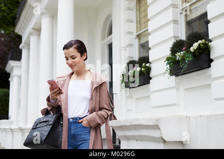 Woman in duster coat and jeans using smartphone in street - Stock Image