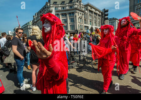 London, UK. 19th April 2019. Figures in red to represent the blood of exticnt species walk around Oxford Circus at Extinction Rebellion's Sea of Protest after police surrounded the yacht. They police began the slow process of persuading protesters to leave by threatening them with arrest and cutting off those who were locked on around the bottom of the yacht. There were a number of arrests of protesters who refused to leave. A few tried to get the large crowd to protect the yacht, but XR organisers persuaded them not to physically oppose the police action. Peter Marshall/Alamy Live News - Stock Image