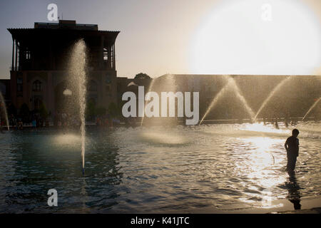 Ali Qapu Palace and public fountains in Naqsh-e Jahan Square. Imam Square, Isfahan city, Iran. Iranian boy in water. - Stock Image