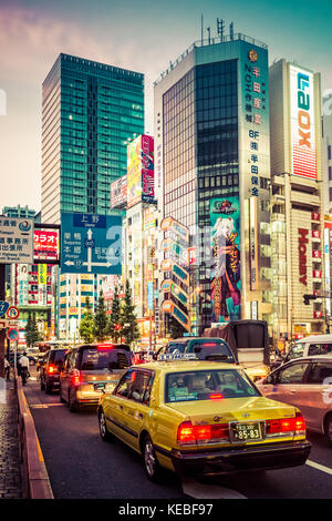 A taxi stuck in the evening rush hour traffic in Akihabara with the bright neon advertisements in the background - Stock Image
