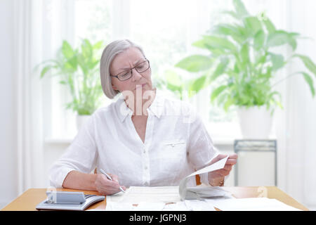 Senior woman at home with a calculator and lots of bills and receipts, filling out the printed forms of the annual - Stock Image