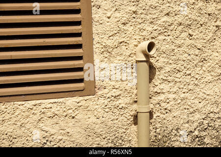 External Natural Gas Meter With Some Yellow Steel Pipes on Wall - Stock Image