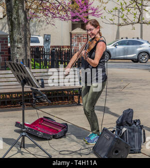 ASHEVILLE, NC, USA-4/11/19:  A smiling woman plays a violin in early spring in downtown Asheville. - Stock Image