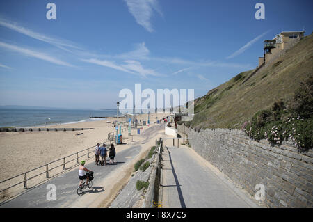 People make their way along Fisherman's Walk beach in Southbourne, which has been awarded a Blue Flag award by Keep Britain Tidy. - Stock Image