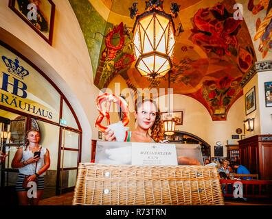Munich, Germany - July 29, 2018: Young attractive waitress sells giants pretzels at the iconic Hofbrauhaus beer hall in Munich, Germany - ultra wide - Stock Image