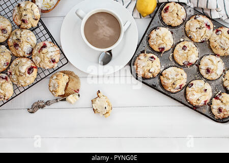 Hot steaming coffee and cranberry muffins with butter over a rustic white table  background. Image shot from above with free space for text. - Stock Image