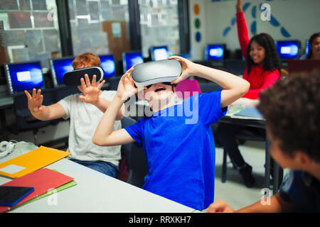 Junior high school boy students using virtual reality simulators in classroom - Stock Image