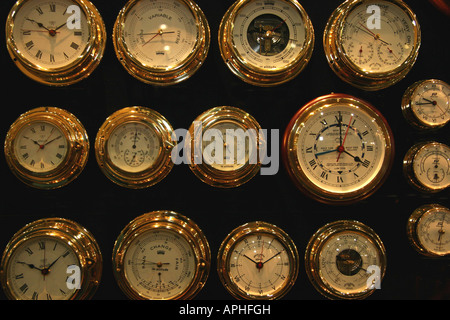 a selection of round brass clocks and dials for boat - Stock Image
