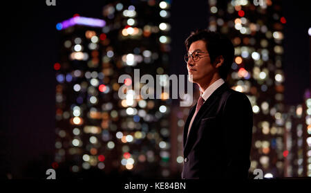 Side view portrait of businessman against night view of city - Stock Image