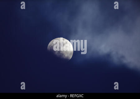 Moon on night sky against dark clouds - Stock Image