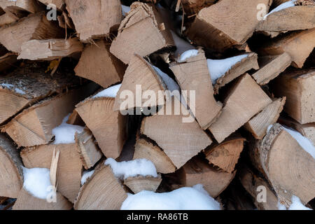 Stacked firewood in a winter woodpile - Stock Image