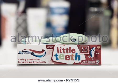 Poznan, Poland - March 8, 2019: Aquafresh little teeth toothpaste in a box and toothbrush in soft focus background. - Stock Image