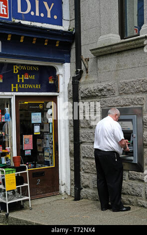 A man using a  cash machine in Camborne, Cornwall, UK - Stock Image