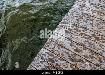 Rain drops begin to dampen boat dock, Dore Lake, Saskatchewan, Canada - Stock Image