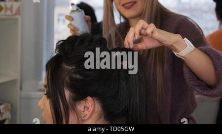 Hair stylist apply fixing hairspray. Fishbone braid. Image completion. Final touch. Hairdressing services. Beauty industry - Stock Image