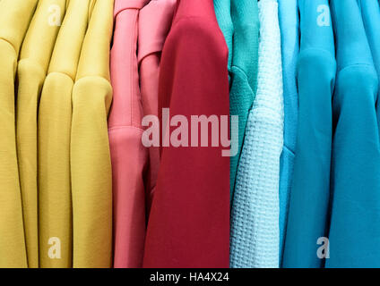 Vertical rows of brightly colored womens coats and clothes inside a shop interior. - Stock Image
