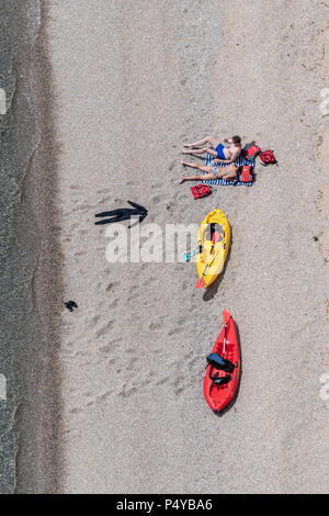Lulworth, Dorset, UK. 23rd June 2018. Two people relax on the beach with their kayaks at Durdle Door on the Dorset coast, near Lulworth Cove on a hot sunny day in June. Thomas Faull/Alamy Live News - Stock Image
