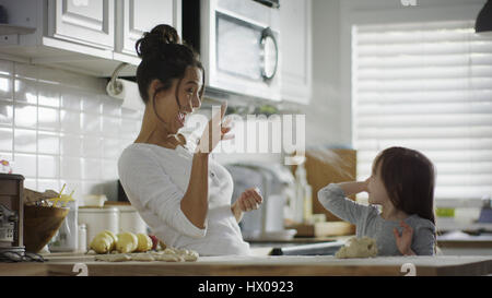 Blurred playful mother and daughter baking and tossing dough in kitchen - Stock Image