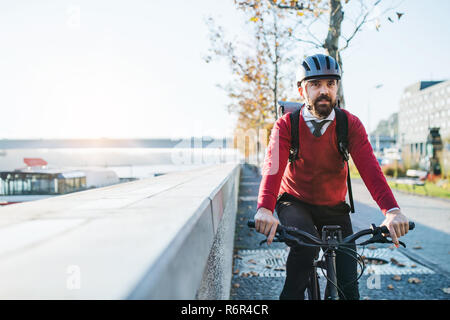 A front view of hipster businessman commuter with electric bicycle traveling to work in city. Copy space. - Stock Image