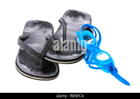 Old black worn boy's sea slippers isolated on white background. Glasses for the sea. White background. - Stock Image