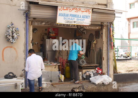Indian workers in a scrap metal shop, Muharraq souk, Kingdom of Bahrain - Stock Image