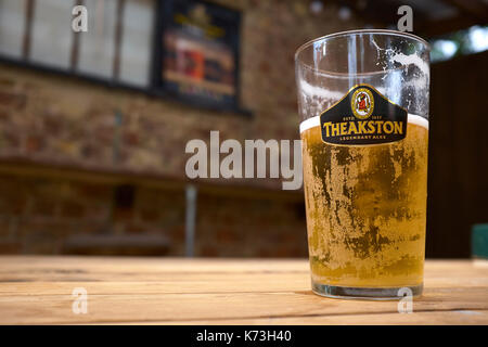 A half-finished pint of Theakston's ale beer on a wooden table, in a Yorkshire pub public house, United Kingdom. - Stock Image